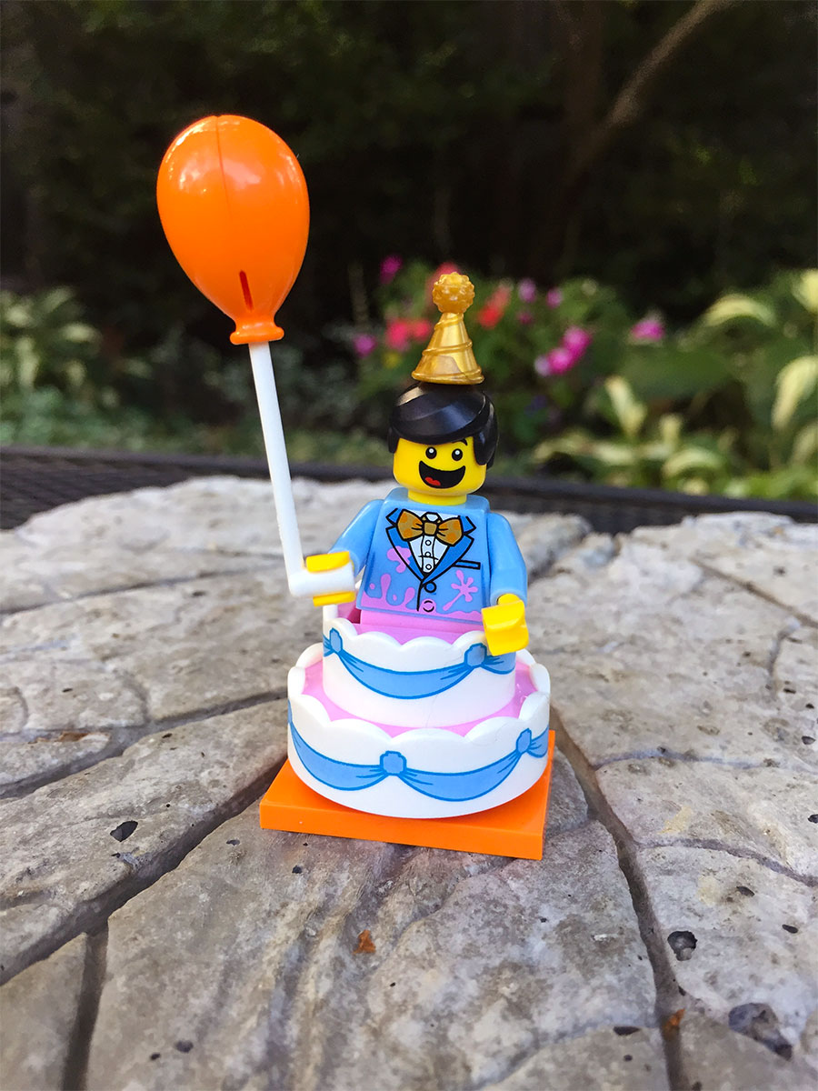 A photo of a LEGO figure jumping out of a birthday cake with balloon in hand.